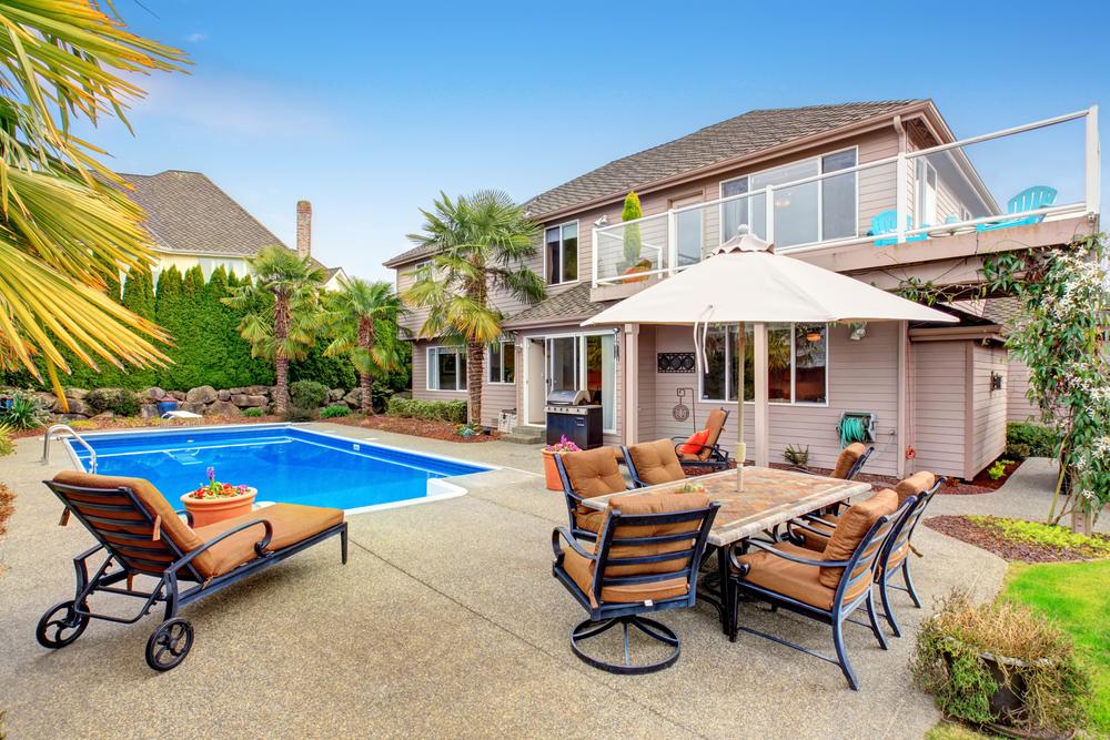 Jardin aménagé, avec une piscine entourée de transats.