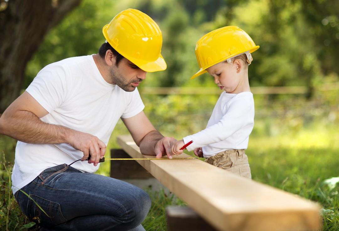 Un père et un fils en train de prendre des mesures sur une planche de bois.