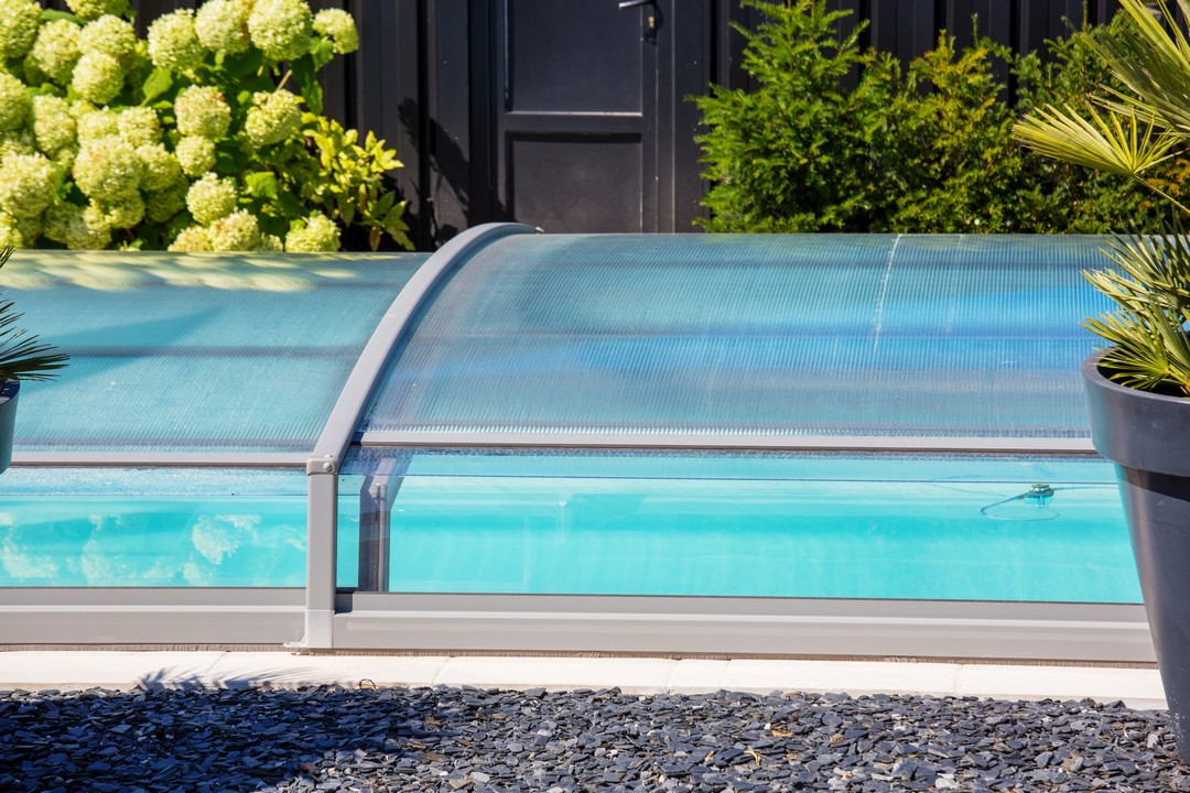 Un abri bas rectangulaire recouvre une piscine.