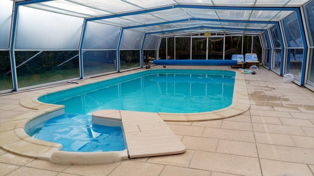 Un abri rectangulaire couvre une piscine.